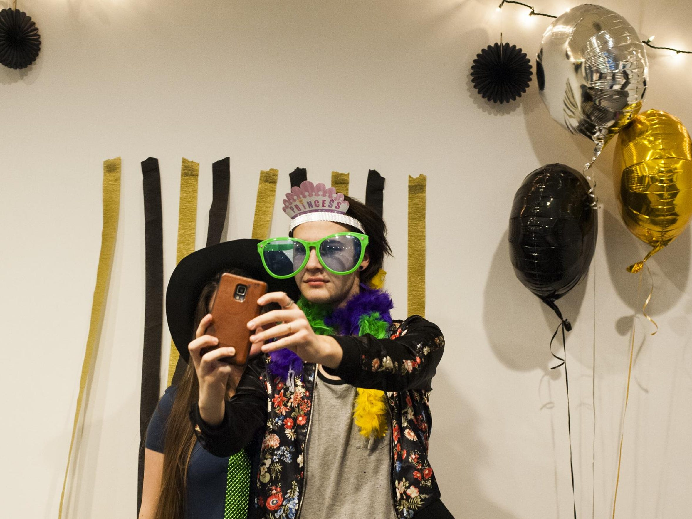 Echo Sundstrom, adorned with photo booth props, takes