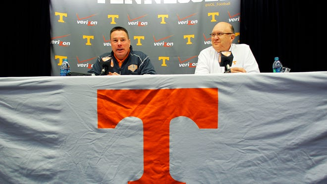Vols coach Butch Jones, left, speaks during a press conference introducing Mike Debord, right, as the new offensive coordinator Friday.