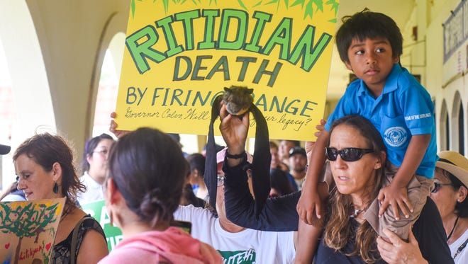 Biologist Suzanne Medina holds up a stuffed-toy fruit bat, or locally called fanihi, as she and her son, Luan Medina, join others during a Prutehi Litekyan: Save Ritidian's peaceful protest outside the governor's office at Adelup on Tuesday, Aug. 29, 2017. The protesters were hoping to call upon Gov. Eddie Calvo to put a stop to the live-fire training range complex slated to be built on Northwest Field of Andersen Air Force Base in Yigo, but the governor was out of the office at the time of the protest.
