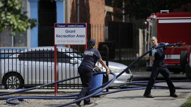 Cincinnati firefighters use bleach and a fire hose to clean and remove pools of blood left at the scene of a mass shooting near Grant Park in Cincinnati on Sunday.