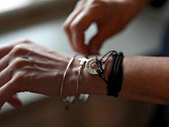 On her wrist, Ann Rowe wears a bracelet with the word