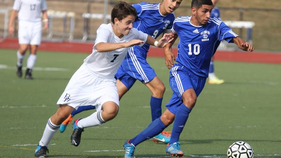 Port Chester's Steven Hernandez, right, moves the ball in front of Bryam Hiills' Zach Beinhacker during the Byram Hills vs. Port Chester boys soccer game in Armonk, Sept. 4, 2015. Byram Hills beat Port Chester 1-0.