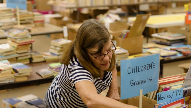 Neenah's Betty Pontius arranges books at the Northland Mall in Appleton in advance of the annual AAUW Appleton Branch book sale.