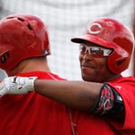 Reds outfielder Marlon Byrd hugs first baseman Joey Votto during batting practice at spring training.