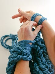 Arm knitting is done by looping yarn around your arms instead of knitting needles.