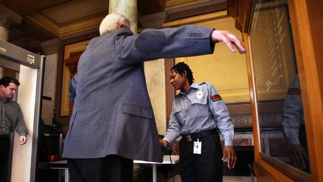 Indiana Statehouse security officer Nichole Polin, right, uses a magnetometer wand to check Roy Dominguez, Crown Point, a former Lake County Sheriff and Indiana State Trooper, who set off the alert while passing through the security check at the east entrance to the Indiana Statehouse on Tuesday, Jan. 3, 2012.