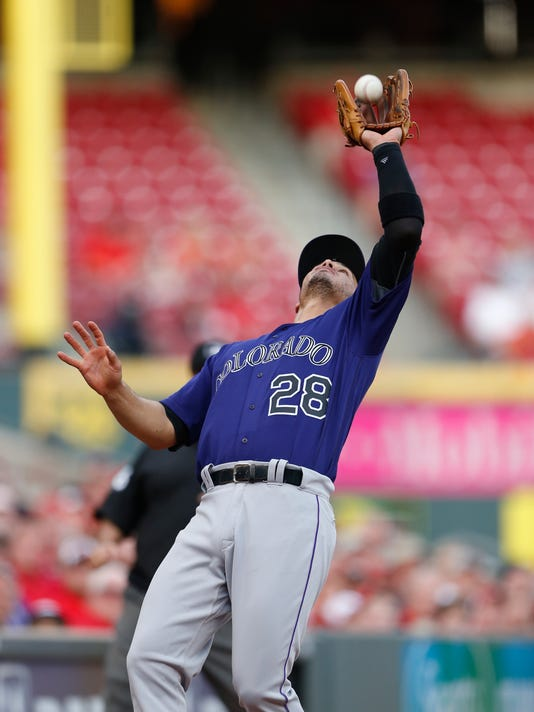 Colorado Rockies third baseman Nolan Arenado (28) catches a pop foul off the bat of Cincinnati Reds shortstop Zack Cozart during the first inning of a baseball game, Monday, April 18, 2016, in Cincinnati. (AP Photo/Gary Landers)