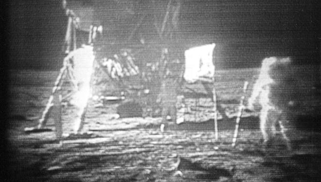FILE - In this July 20, 1969 file photo, Apollo 11 astronaut Neil Armstrong, right, trudges across the surface of the moon leaving behind footprints. Moon dust collected by Armstrong during the first lunar landing is being sold at a New York auction.  The lunar dust plus some tiny rocks that Armstrong also collected are zipped up in a small bag and are worth an estimated $2 million to $4 million. They're just some of the items linked to space travel that Sotheby's is auctioning off to mark the 48th anniversary of the first lunar landing on July 20. (AP Photo, File)