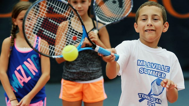 Sam Decou, 9, of Bridgeton returns a serve during a drill Tuesday at the Millville tennis camp.