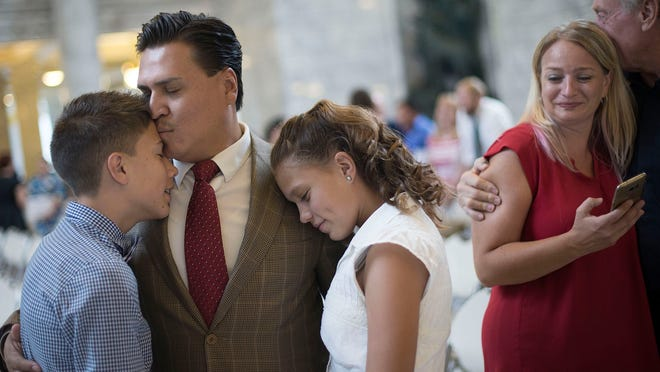 Victor Avalos, of Mexico, hugs his children, Nathan and Isabelle, as his wife, Kelly, is embraced by her father, Guy Davis, after Avalos became a citizen during a naturalization ceremony at the state Capitol in Salt Lake City on Wednesday, July 19, 2017.