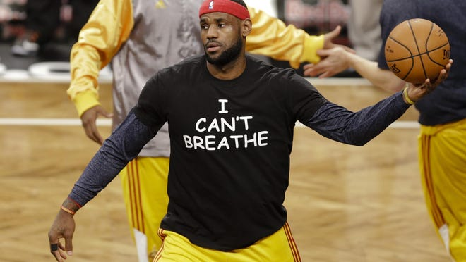 """FILE - In this Dec. 8, 2014 file photo, Cleveland Cavaliers' LeBron James wears a T-shirt reading """"I Can't Breathe,"""" protesting the death of Eric Garner, during warms up before an NBA basketball game against the Brooklyn Nets in New York. Despite their vastly divergent methods, Colin Kaepernick and LeBron James helped set a stake in the ground, declaring to athletes across all sports that their platforms could be used for more than fun and games in the 21st century."""