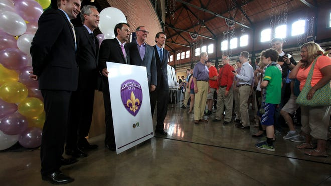 Soccer team dignitaries posed with the template of a logo following a press conference to announce that Louisville City Football Club will start play in 2015.