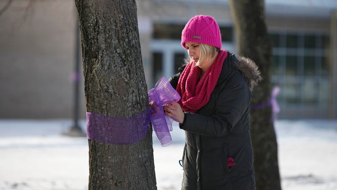 Laura Delehanty, a teacher at East High School, ties purple ribbons on most of the trees surrounding the school to honor the sixth birthday of Amanda Conrow, the daughter of co-worker Paul Conrow. Amanda has been battling brain cancer and is in the end stages of life. Purple is Amanda Conrow's favorite color.