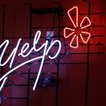 This Oct. 26, 2011 file photo shows the logo of the online reviews website Yelp on a wall at the company's offices in New York.