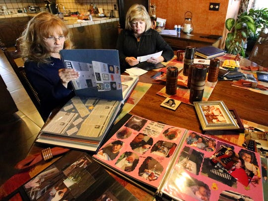 Juni Mathews, left, and Armenia Smith look over photos of their friend and colleague, Deby Lewis, in the late teacher's parents home.
