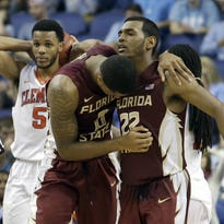 Florida State's Xavier Rathan-Mayes (22) and Phil Cofer (0) celebrate as Clemson's Jaron Blossomgame (5) walks off the court after an NCAA college basketball game in the second round of the Atlantic Coast Conference tournament in Greensboro, N.C., Wednesday, March 11, 2015. Florida State won 76-73. (AP Photo/Bob Leverone)