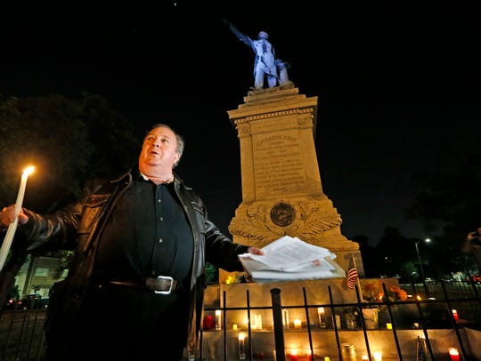 Charles Lincoln speaks during a candlelight vigil at