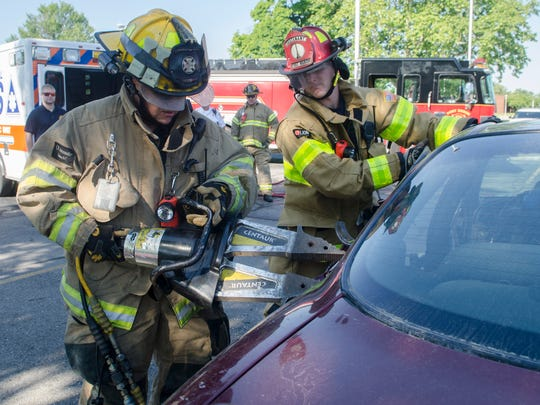 Port Huron Fire Department's John Schuman operates the hydraulic jack with James Hayes Friday morning, June 24, 2016 during a mock accident exercise at St. Clair County Community College.