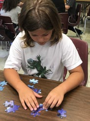 Branson Werner plays with a puzzle at McMurry University's