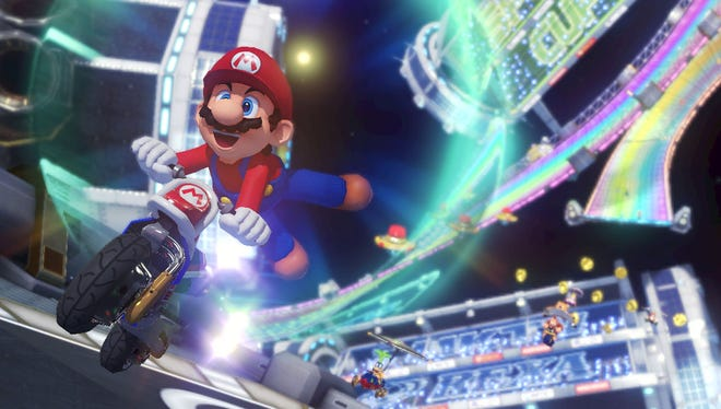 Mario speeds down Rainbow Road on a motorbike in 'Mario Kart 8.'