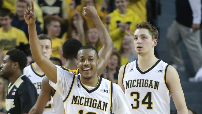 Michigan Wolverines Muhammad-Ali Abdur-Rahkman (12) and Mark Donnal celebrate a win Feb. 13, 2016, at the Crisler Center in Ann Arbor.