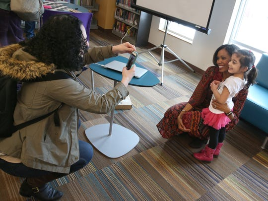 Aesha Ash poses with young Alissa Tuff, 4, as her mother, Alison Tuff, Rochester, takes their photo following Ash's talk about her Swan Dreams Project during her visit to the Central Library of Rochester & Monroe County Saturday, Feb. 3, 2018.  Ash and Tuff once danced together in the same school in Rochester over 30 years ago.