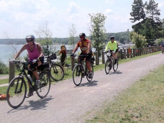 Doug Carnegie (in yellow jersey) rides with other tour