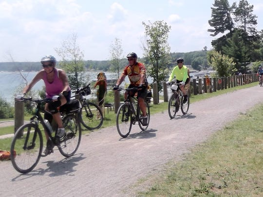 Doug Carnegie (in yellow jersey) rides with other tour participants along Mullett Lake on the North Central State Trail on the first day of the 2-Day Michigander, July 11.