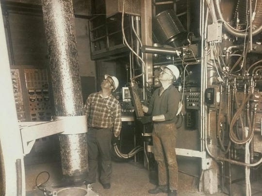 Cliff Albee, left, and a co-worker examine a metal