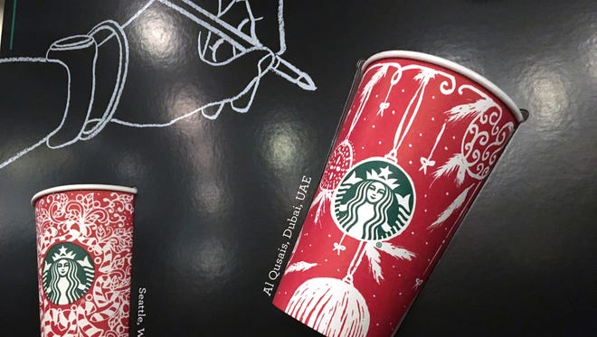 In this Tuesday, Nov. 8, 2016, photo, Starbucks holiday cups appear on display at a store in New York. Snowflakes, reindeer and candy canes are back on Starbucks holiday coffee cups, after last year's plain red cups caused uproar from critics who said the chain was part of a so-called war on Christmas.