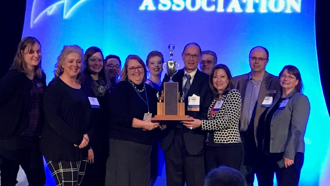 Members of the St. Cloud Times team hold the Vance Trophy, an award given to the best outstate daily news organization in the Minnesota Newspaper Association Better Newspaper Contest.