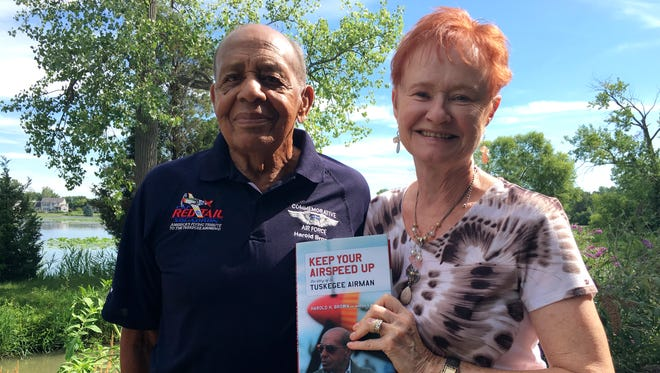 "Marsha Bordner holds up a copy of ""Keep Your Airspeed Up,"" a book she co-authored with her husband, Harold Brown, about his life and experiences during World War II as a Tuskegee Airman."
