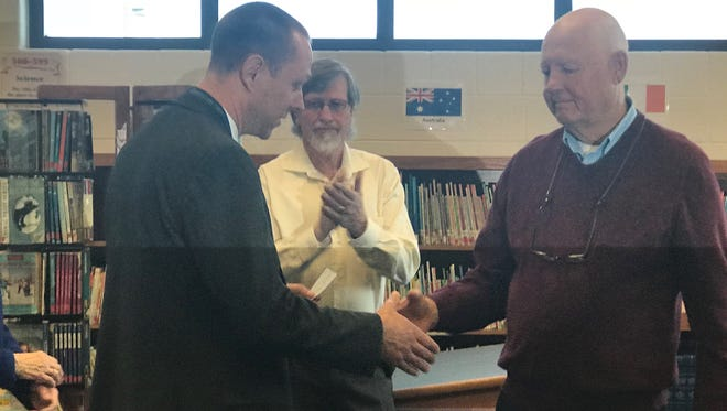 Dale Brinkley (right), presents a check of more than $151,000 on behalf of Douglas and Opal Shearron to Pleasant View Elementary School Principal Keith Miller (left) on April 11, 2018 in the Opal Nichols Shearron Memorial Library in Pleasant View Elementary School. Opal Shearron, a former teacher whose career in the Cheatham County School District spanned more than three decades, died in 2007. The school will use the donation to incorporate technology into the library for students.