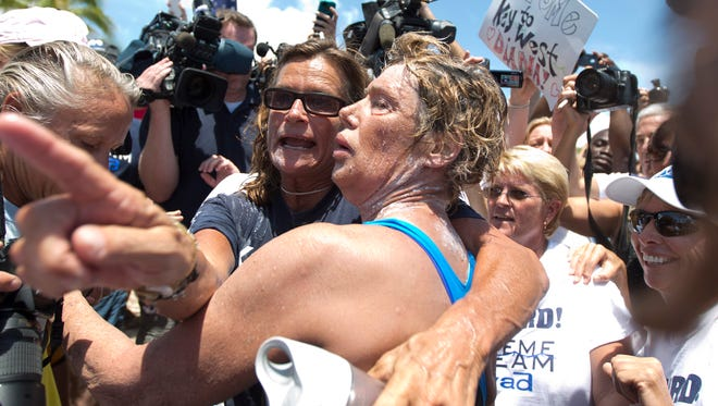 Nyad, right, and her trainer, Bonnie Stoll hug after Nyad walks ashore in Key West, Fla.