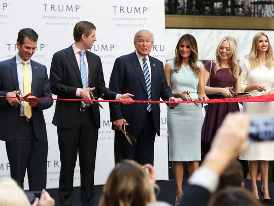 Donald Trump, together with his family, from left, Donald Trump Jr., Eric Trump, Melania Trump, Tiffany Trump and Ivanka Trump, speaks in the hotel lobby during the grand opening of Trump International Hotel in Washington on Oct. 26, 2016.
