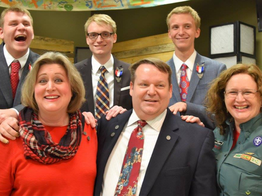 Chris Barrett, top left, Andy Barrett and Phil Barrett pose with their mother Becky Barrett, bottom left, father Ian Barrett and Venturing Crew Adviser Rebecca Phinney at their Eagle Scout Rank award ceremony.