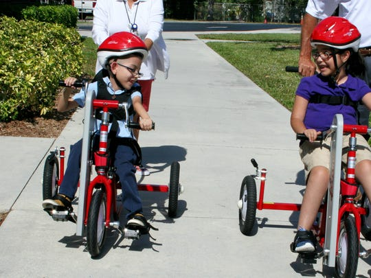 Anthony and Itzel Castillo ride their bikes together on the sidewalk in front of Avalon Elementary School.
