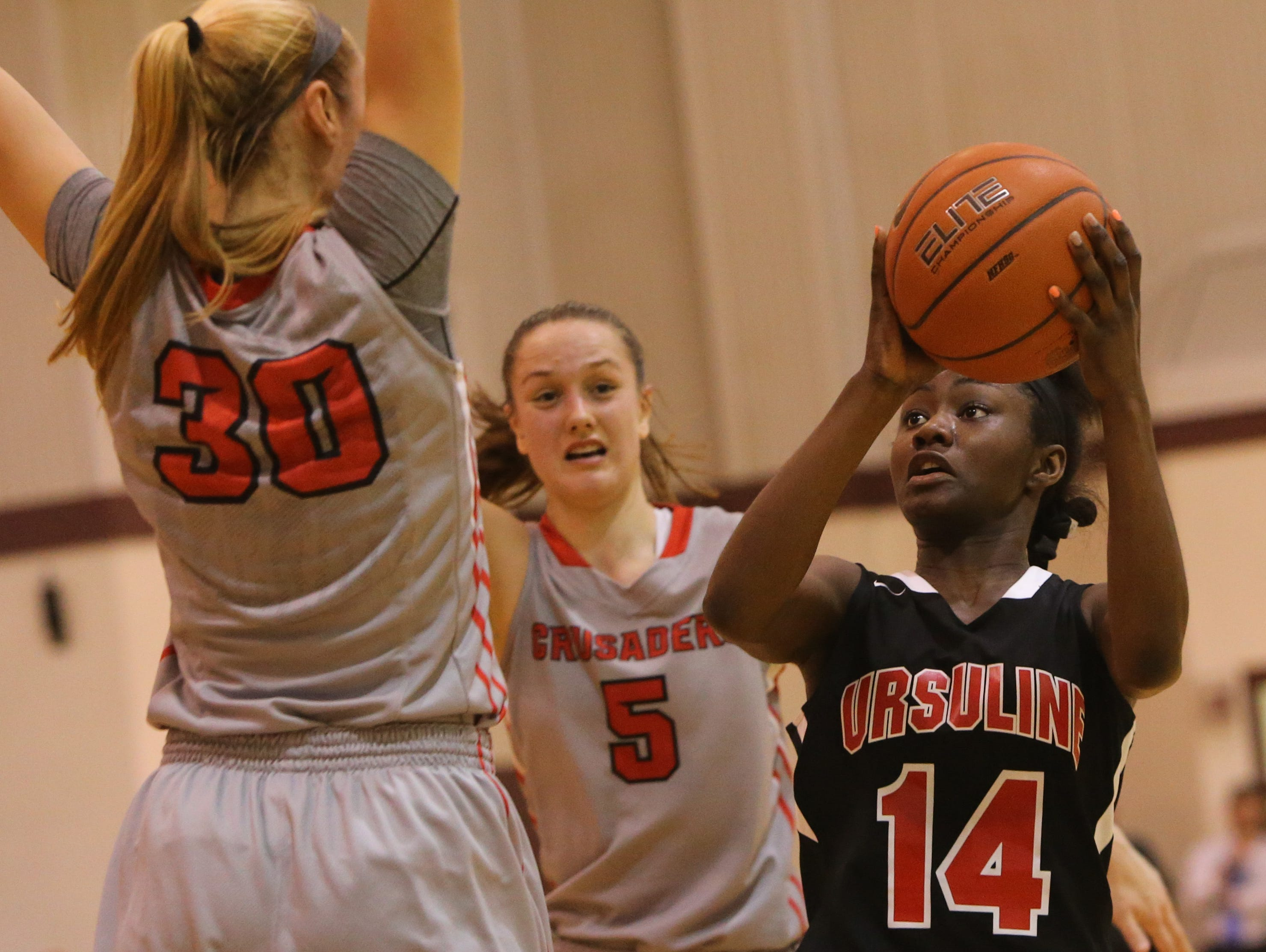 Ursuline forward Kryshell Gordy is surrounded by Long Island Lutheran defenders Aislinn Flynn, No. 30, and Sarah Mortensen in the second quarter. Ursuline falls to Long Island Lutheran 52-55 in the semifinals of the Saint Francis Healthcare Cup of the Diamond State Classic at St. Elizabeth High School Tuesday.