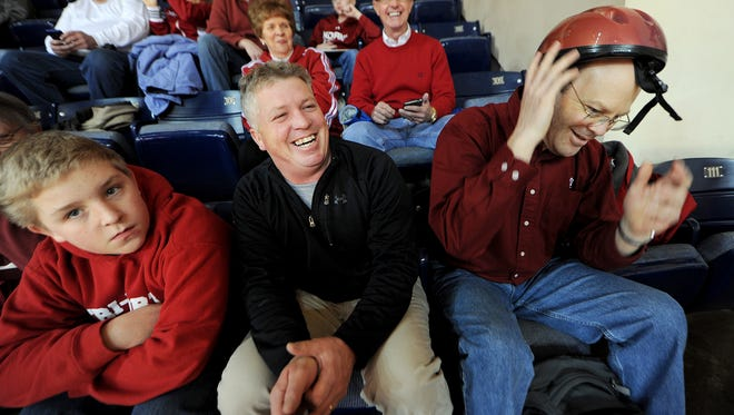 IU fan Mike Rogers, of Bloomington, gets laughs from other fans when he pulls out a bicycle helmet in case another piece of metal flashing falls on his seat prior to the Iowa game at Assembly Hall, Thursday, February 27, 2014, in Bloomington. A piece of metal fell onto Rogers seat on February 18 when the  hall was not in use.