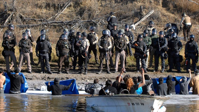 Dakota Access Pipeline protesters stand waist deep in the Cantapeta Creek, northeast of the Oceti Sakowin Camp, near Cannon Ball, N.D., Wednesday, Nov. 2, 2016. Officers in riot gear clashed again Wednesday with protesters near the Dakota Access pipeline, hitting dozens with pepper spray as they waded through waist-deep water in an attempt to reach property owned by the pipeline's developer.