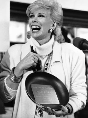 Comedian Joan Rivers reacts after presented with a frying pan, honoring her with the 'First Instant Pudding Award University's' Hasty Pudding Theatricals on Tuesday, June 3, 1986 in Cambridge. Rivers, who received the original Pudding Award in 1984, was in Cambridge, Massachusetts to promote her new book in a square bookstore.