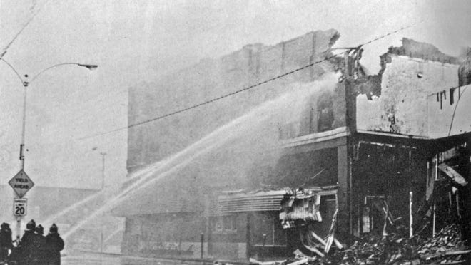 Firefighters train their water cannons on the remains of the Centennial Block.