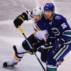 St. Louis Blues forward Patrik Berglund (21) battles for the puck against Vancouver Canucks forward Jannik Hansen (36) during the third period at Rogers Arena.