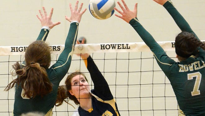 South Lyons Chloe Grimes, who had 15 kills, puts a shot through Howell's front line in a district championship victory.