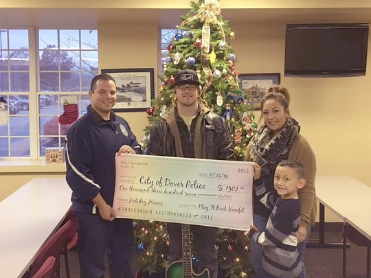 "M/Cpl. Mark Hoffman of the Dover Police Department receives a check in the amount of $1,307 from Dave Nickolson, Kathy Nicolson, and their son Kadence. The money was raised through a ""Play It Back"" benefit concert for the DPD ""Holiday Heroes"" program."