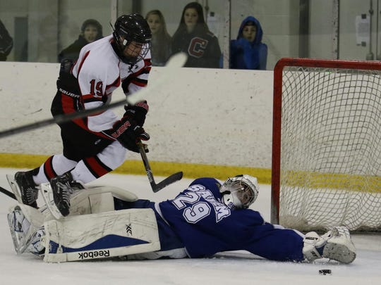 Reaching to corral a loose puck is Salem goalie Austin