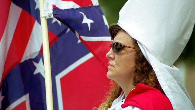 A female member of the Ku Klux Klan stands at attention at a rally in Elwood.