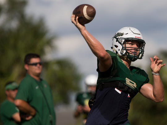 Jensen Jones, the junior quarterback for St. John Neumann High School, throws a ball during practice as head coach Damon Jones, back left, also Jones' father, watches at St. John Neumann's Monday, October 9, 2017 in East Naples. Jones, who is playing his first year at quarterback, has played a large role in leading the team to an undefeated 4-0 start to the season.