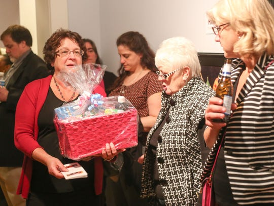 Lois Place holds the gift basket she won in the raffle