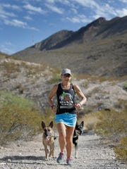 Constance Wannamaker runs in the Franklin Mountains with her dogs Annie and Freddy just a week after a 100-mile race.
